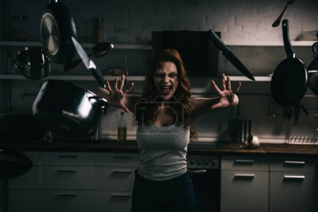 Photo for Creepy demoniacal yelling girl with levitating kitchenware in kitchen - Royalty Free Image