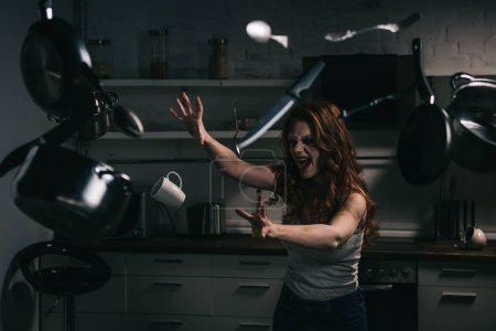 Photo for Creepy yelling girl gesturing with levitating kitchenware in kitchen - Royalty Free Image