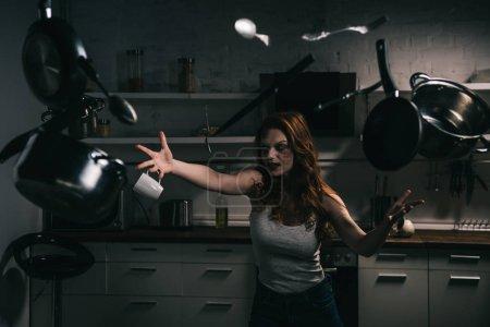 Photo pour Fille démoniaque effrayant avec des pots lévitants et des couteaux dans la cuisine - image libre de droit