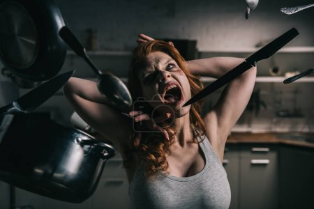 Photo for Demoniacal yelling girl with levitating kitchenware in kitchen - Royalty Free Image
