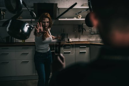 selective focus of female demon with levitating cookware and exorcist with cross in kitchen