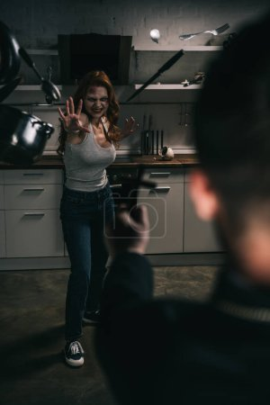 selective focus of creepy demoniacal girl with levitating cookware and exorcist with cross in kitchen