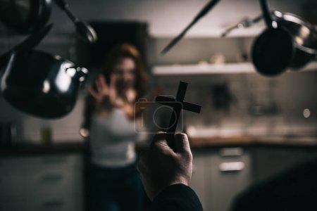 Photo pour Foyer sélectif de démon femelle avec ustensiles de cuisine lévitante et exorciste avec croix dans la cuisine - image libre de droit