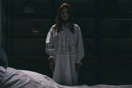 Photo pour Femme obsédée en chemise de nuit debout près du lit dans la chambre noire - image libre de droit
