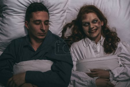 Photo for Top view of creepy smiling female demon lying in bed with sleeping man - Royalty Free Image