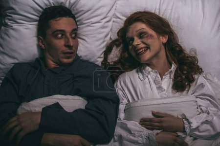 Photo pour Top view of female smiling demon lying in bed with scared man - image libre de droit