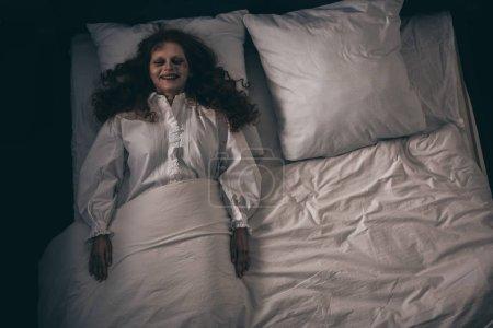 Photo pour Vue de dessus de démon souriant effrayant en chemise de nuit couché dans le lit - image libre de droit