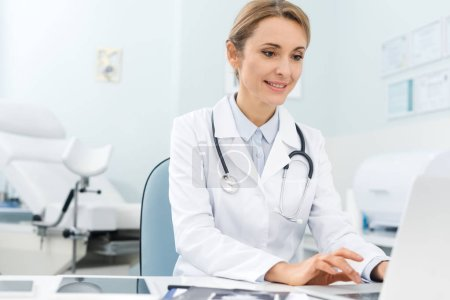 Photo pour Beau médecin professionnel travaillant sur ordinateur portable en clinique - image libre de droit
