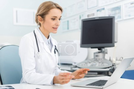 Photo pour Belle femme médecin travaillant sur ordinateur portable en clinique avec échographie scanner - image libre de droit