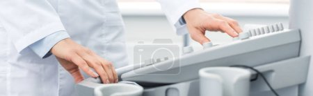 Photo for Partial view of professional doctor working with ultrasound scanner in clinic, panoramic shot - Royalty Free Image