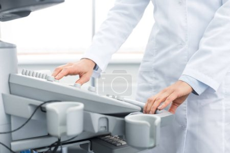 Photo for Cropped view of doctor in white coat working with ultrasound scanner in clinic - Royalty Free Image