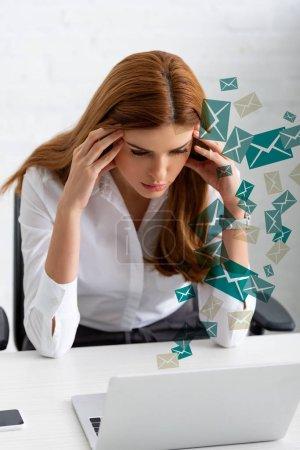 Photo pour Femme d'affaires pensive avec les mains près de la tête regardant un ordinateur portable sur la table, illustration de courrier - image libre de droit
