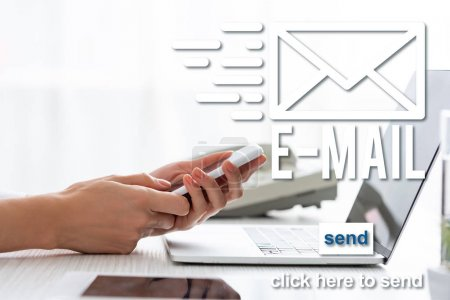 Cropped view of businesswoman using smartphone near digital tablet and laptop on table, e-mail illustration