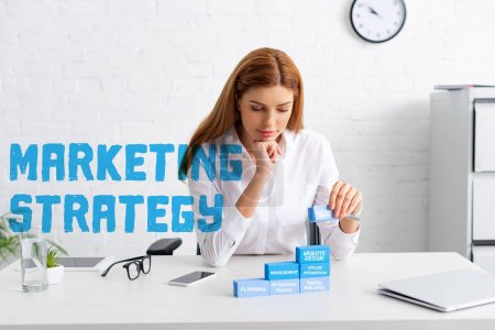 Photo pour Attractive business woman stacking marketing pyramid from blue building blocks on table, marketing strategy illustration - image libre de droit