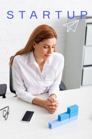 Photo pour Belle femme d'affaires regardant empilés blocs de construction bleus sur la table de travail, illustration de démarrage - image libre de droit