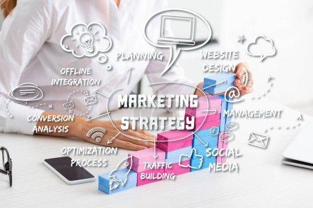 Photo pour Vue recadrée de femme d'affaires empilant la pyramide de vente des blocs de construction sur la table, illustration de stratégie de marketing - image libre de droit
