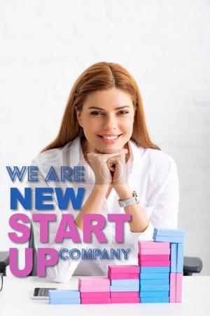 Photo pour Femme d'affaires souriant devant une caméra près de la pyramide du marketing à partir de blocs de construction sur la table, nous sommes une nouvelle entreprise de démarrage illustration - image libre de droit