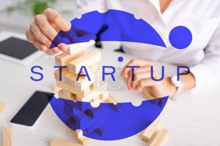 Photo pour Focus sélectif de femme d'affaires jouant blocs tour de bois jeu à table, illustration de démarrage - image libre de droit