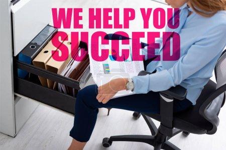 Photo pour Vue à grand angle d'une femme d'affaires tenant des documents avec des cartes alors qu'elle est assise près d'un conducteur de cabinet ouvert, nous vous aidons à réussir l'illustration - image libre de droit