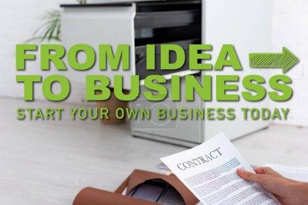 Photo pour Vue recadrée de femme d'affaires détenant un contrat près de dossiers en papier sur le sol, de l'idée à l'illustration d'entreprise - image libre de droit