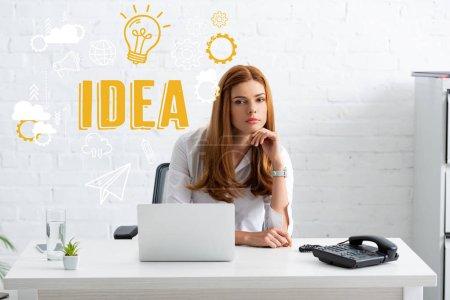 Photo pour Femme d'affaires avec la main près du menton regardant la caméra près de l'ordinateur portable et le téléphone sur la table, illustration d'idée - image libre de droit