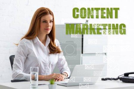 Photo pour Femme d'affaires attrayante regardant loin à table avec ordinateur portable et téléphone, illustration de marketing de contenu - image libre de droit
