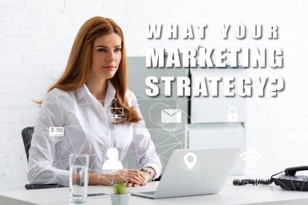 Photo pour Une femme d'affaires attrayante qui regarde loin sa table avec son ordinateur portable et son téléphone, ce que sa stratégie de marketing illustre - image libre de droit