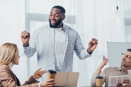 Photo for African american man talking with colleagues during meeting in creative agency - Royalty Free Image