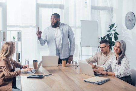 Photo for African american man showing idea and talking with colleagues during meeting in creative agency - Royalty Free Image