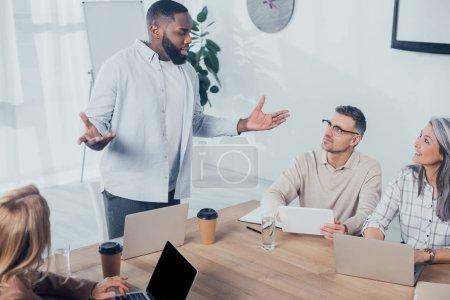 Photo pour Africain américain parlant avec des collègues lors d'une rencontre dans une agence de création - image libre de droit