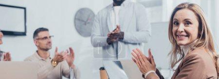 Photo pour Plan panoramique de la femme souriante applaudissant avec des collègues multiculturels - image libre de droit