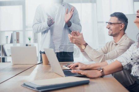 Photo pour Croisée des points de vue de collègues multiculturels souriants claquant lors d'une réunion dans une agence créative - image libre de droit