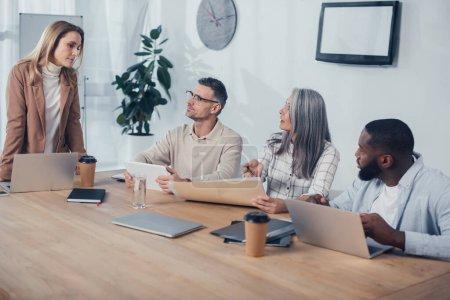 Photo pour Collègues multiculturels discutant lors d'une réunion dans une agence créative - image libre de droit
