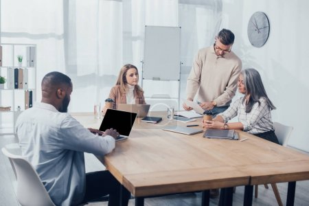 Photo for Multicultural colleagues doing paper work and african american man using laptop - Royalty Free Image