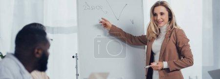 Photo pour Plan panoramique d'une femme d'affaires souriante pointant du doigt le lettrage des objectifs et parlant avec un collègue afro-américain - image libre de droit