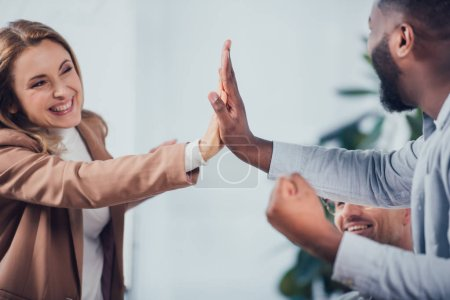 Photo for Cropped view of smiling multicultural colleagues giving high five in creative agency - Royalty Free Image