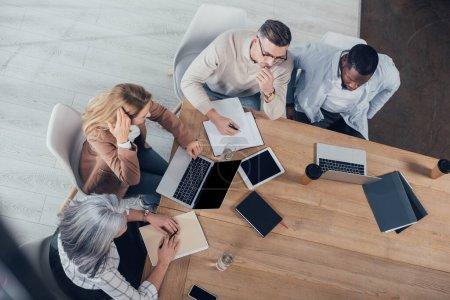 Photo pour Vue aérienne de collègues multiculturels parlant et s'asseyant à la table pendant la réunion - image libre de droit