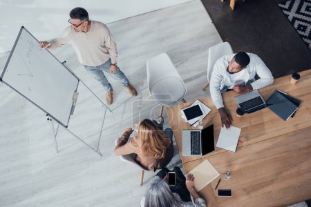 overhead view of multicultural colleagues sitting at table and looking at businessman during presentation