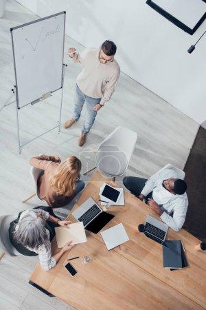 Photo pour Vue aérienne de collègues multiculturels assis à la table et regardant l'homme d'affaires pendant la présentation - image libre de droit