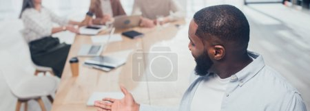 Photo pour Photo panoramique d'un homme d'affaires américain africain souriant regardant ses collègues - image libre de droit
