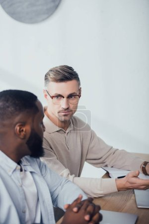 Photo for Multicultural colleagues talking and sitting at table in creative agency - Royalty Free Image