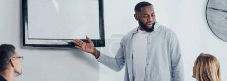 Photo pour Plan panoramique d'un homme d'affaires afro-américain souriant pointant du doigt la télévision et parlant avec ses collègues - image libre de droit