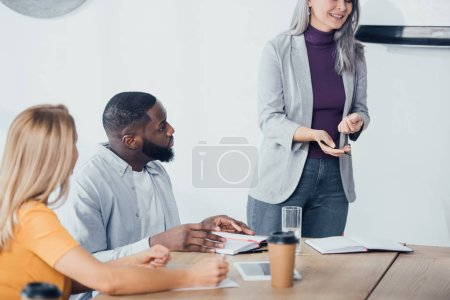 Photo for Cropped view of smiling businesswoman talking with multicultural colleagues - Royalty Free Image