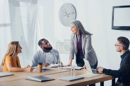 Photo pour Une femme d'affaires asiatique souriante s'entretient avec des collègues multiculturels en poste - image libre de droit