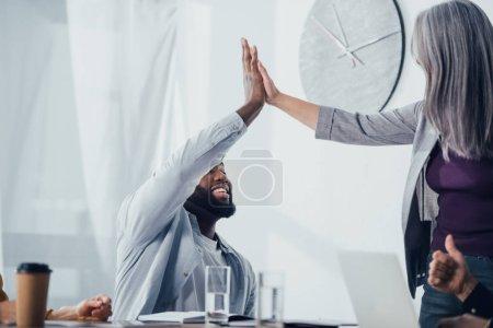 Photo pour Souriant collègues multiculturels donnant haute cinq dans le bureau - image libre de droit