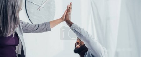 panoramic shot of smiling multicultural colleagues giving high five in office