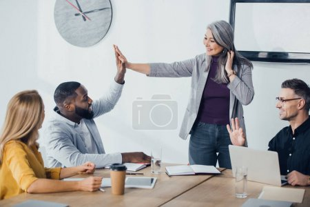 Photo for Smiling multicultural colleagues giving high five and showing ok in office - Royalty Free Image