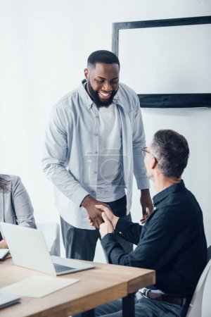 smiling african american businessman shaking hands with his colleague