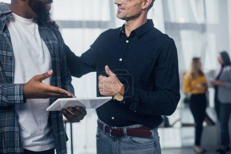 Photo pour Vue recadrée de sourire homme d'affaires afro-américain pointant avec la main à la tablette numérique et ses collègues montrant comme - image libre de droit