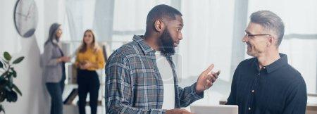 Panoramaaufnahme eines afrikanisch-amerikanischen Geschäftsmannes im Gespräch mit seinem lächelnden Kollegen mit einem digitalen Tablet